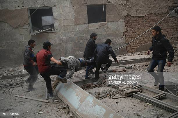 TOPSHOT Syrians evacuate victims following air strikes on the town of Douma in the eastern Ghouta region a rebel stronghold east of the capital...