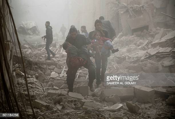 Syrians evacuate victims following air strikes on the town of Douma in the eastern Ghouta region a rebel stronghold east of the capital Damascus on...