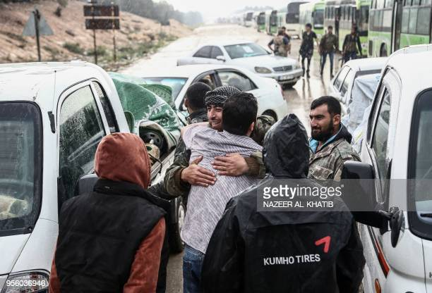 Syrians evacuated from rebelheld areas from Syria's central Homs province in a convoy of buses greet loved ones as they arrive at Abu alZandin...