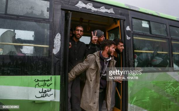 A Syrians evacuated from rebelheld areas from Syria's central Homs province in a convoy of buses flashes the victory gesture as he arrives at Abu...