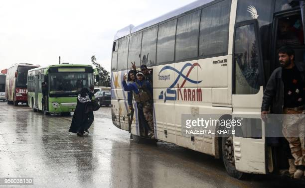 Syrians evacuated from rebelheld areas from Syria's central Homs province flash the victory gesture as their convoy of buses arrives at Abu alZandin...