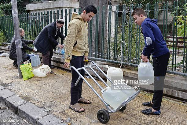 Syrians fill plastic containers with water at a public fountain in the capital Damascus on January 3 2017 The regime of President Bashar alAssad is...