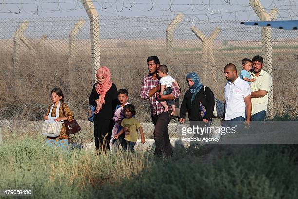 Syrians fled from clashes in Tell Abyad region of Syria carry their belongings after they cross Turkish Syrian border to take shelter in Turkey on...