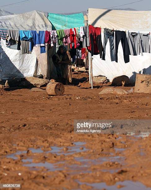 Syrians fled from the clashes in their country walk in mud around the tent camps in Aleppo Syria on December 25 2014 Refugees mostly women and...
