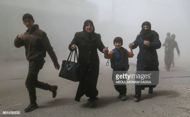 Syrians flee following a reported government air strike on the rebelcontrolled town of Hamouria in the eastern Ghouta region on the outskirts of the...