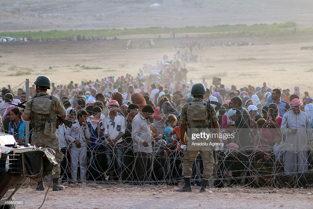 Syrians fleeing from clashes between the Islamic State of Iraq and Levant (ISIL) militants and Democratic Union Party (PYD) forces in the Ar-Raqqah Governorate of Syria, wait at the Turkish-Syrian border to cross into Turkey on September 18, 2014 near Turkey's Sanliurfa province.