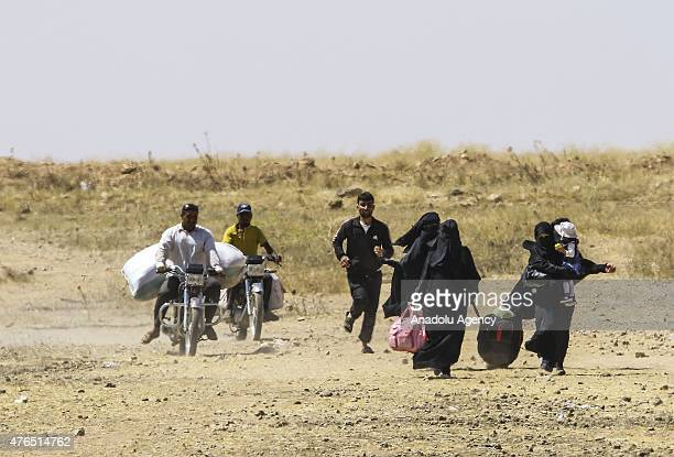 Syrians fleeing the clashes in Rasulayn region of Syria carry their belongings as they arrive at the Syrian side of the TurkishSyrian borderline to...
