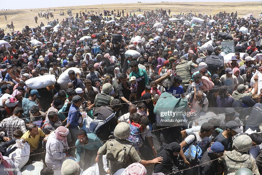 Syrians fleeing the clashes in Rasulayn region of Syria, cross into Turkey from the borderline in Akcakale district of Sanliurfa on June 10, 2015. Hundreds of Syrians who fled from Syria after clashes in Rasulayn region of Al-Hasakah, have crossed into Turkey since last week.