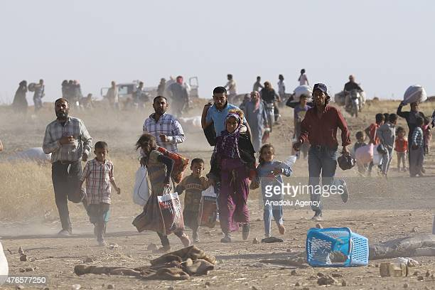Syrians fleeing the clashes in Rasulayn region of Syria cross into Turkey from the borderline in Akcakale district of Sanliurfa on June 10 2015...