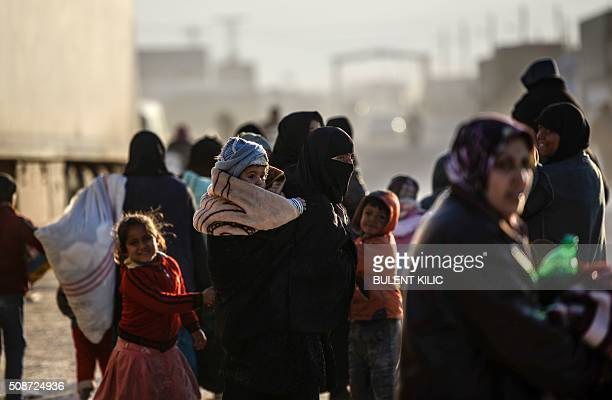 Syrians fleeing the northern embattled city of Aleppo wait on February 5 2016 in BabAl Salama next to the city of Azaz northern Syria near Turkish...