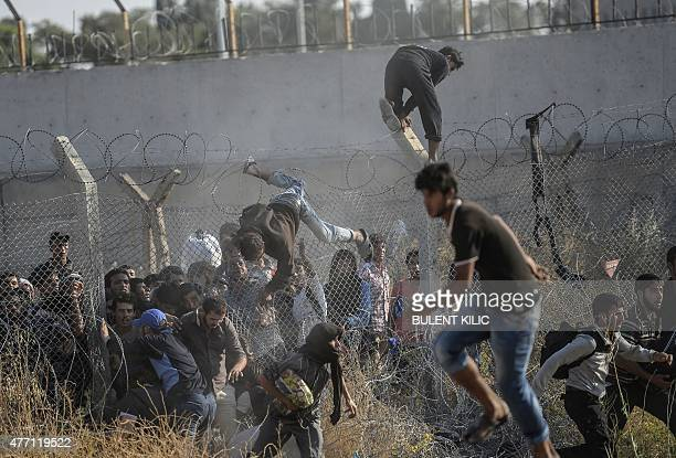 Syrians fleeing the war climb over border fences to enter Turkish territory illegally near the Turkish border crossing at Akcakale in Sanliurfa...