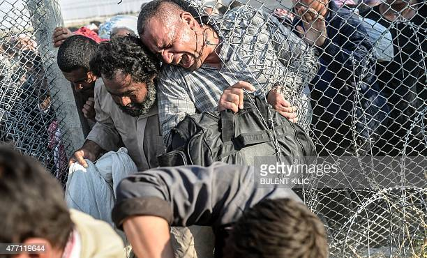 Syrians fleeing the war pass through border fences to enter Turkish territory illegally near the Turkish border crossing at Akcakale in Sanliurfa...