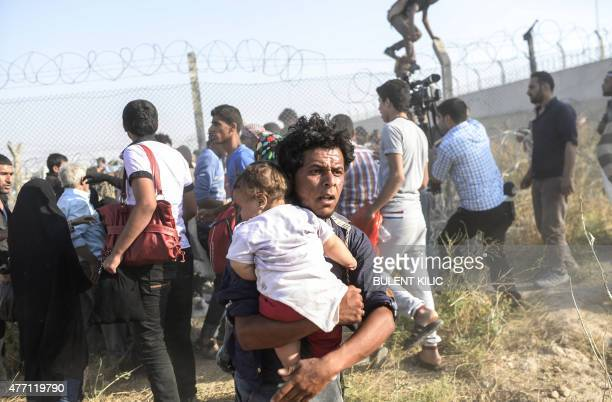 Syrians fleeing the war pass through border fences to enter Turkish territory illegally, near the Turkish border crossing at Akcakale in Sanliurfa...