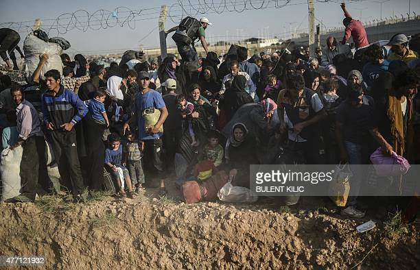 Syrians fleeing the war pass through broken border fences to enter Turkish territory illegally near the Turkish border crossing at Akcakale in...