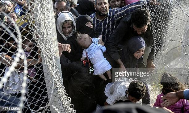 Syrians fleeing the war rush through broken down border fences to enter Turkish territory illegally near the Turkish border crossing at Akcakale in...