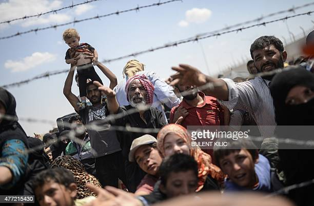 Syrians fleeing the war wait to enter Turkey near the Turkish border crossing at Akcakale in Sanliurfa province on June 15 2015 Turkey said it was...