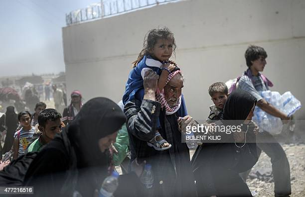Syrians fleeing the war walk towards the border gates at the Akcakale border crossing in Sanliurfa province on June 15 2015 Turkey said it was taking...