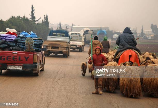 Syrians fleeing with their belongings pass through the town of Batabo in the Aleppo province on February 5 on their way northwards toward the Turkish...