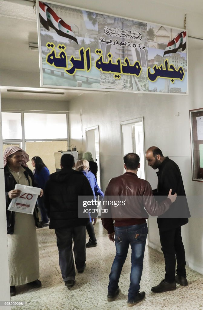 Syrians from Raqa province stand at the entrance of the temporary location of the Raqa governorate administration, some 220 kilometres (135 miles) from their original premises in the city that was the first provincial capital to be lost by the government in March 2013, in a building provided by the Hama governorate administration in the city of Hama in central Syria on March 13, 2017. /
