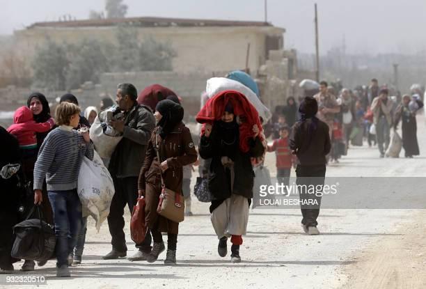 TOPSHOT Syrians from rebelheld Eastern Ghouta walk through a regimecontrolled corridor in Hawsh alAshaari east of the Eastern Ghouta town of Hamouria...