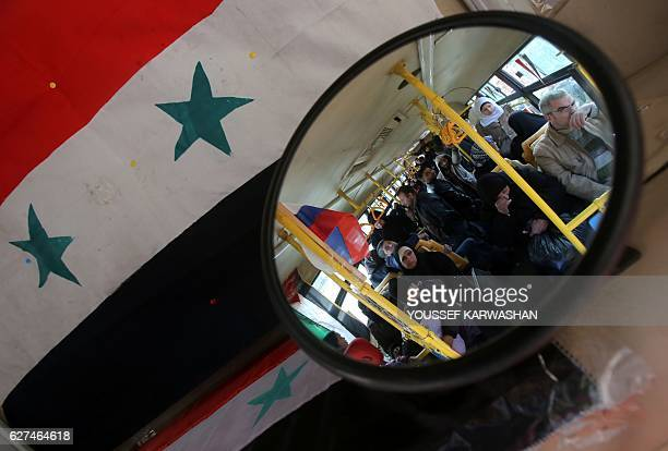 Syrians from various western districts wait on a bus at the Razi bus stop in Aleppo's central Jamiliyeh neighbourhood before the start of a bus trip...
