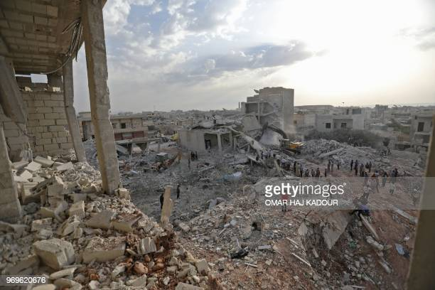 TOPSHOT Syrians gather amidst destruction in Zardana in the mostly rebelheld northern Syrian Idlib province in the aftermath of air strikes in the...