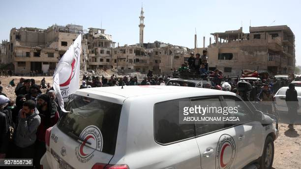Syrians gather around Syrian Red Crescent vehicles as they prepare to evacuate from the town of Arbin in the Eastern Ghouta region on the outskirts...