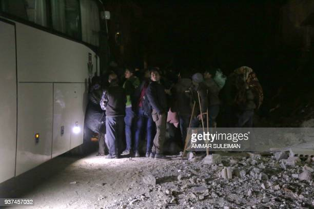 Syrians gather as they prepare to board a bus to evacuate one of the few remaining rebelheld pockets in Arbin in Eastern Ghouta on the outskirts of...