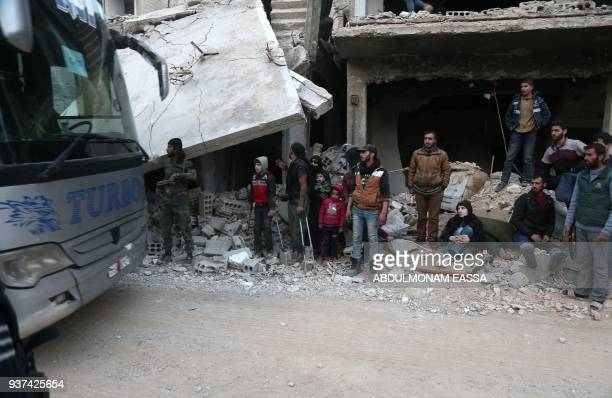 Syrians gather as they prepare to evacuate one of the few remaining rebelheld pockets in Arbin in Eastern Ghouta on the outskirts of the Syrian...