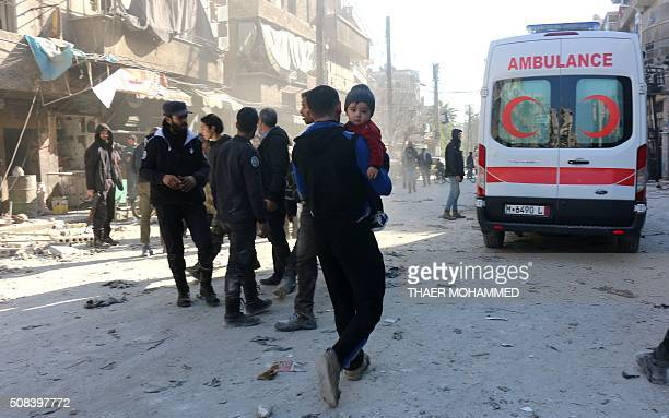 Syrians gather at the site following a reported air strike on the rebelheld neighbourhood of alKalasa in the northern Syrian city of Aleppo on...