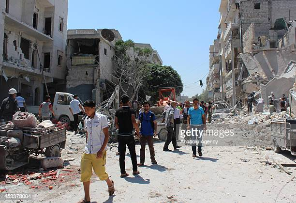 Syrians gather at the site of a barrel bombattack staged by Assad regime forces on a market in Maadi neighborhood of Aleppo Syria on August 9 2014 At...