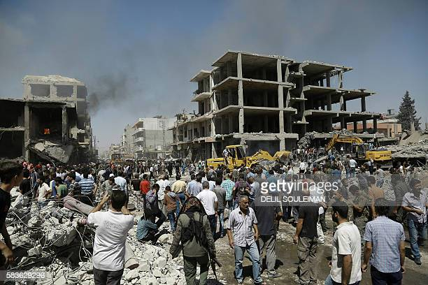 TOPSHOT Syrians gather at the site of a bomb attack in Syria's northeastern city of Qamishli on July 27 2016 A double bomb attack killed at least 14...