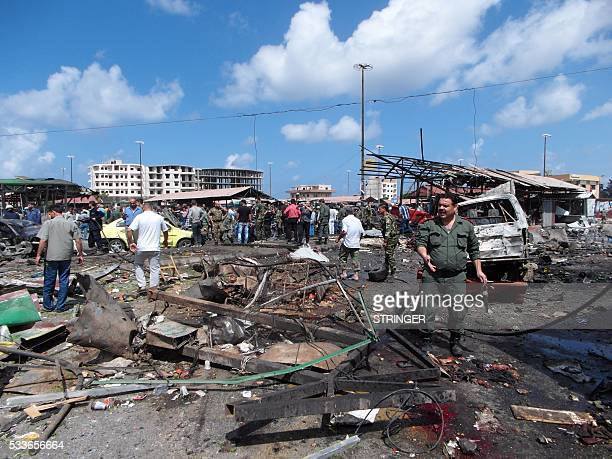 Syrians gather at the site of multiple bombings that left tens dead in the northern coastal city of Jableh between Latakia and Tartus on May 23 2016...