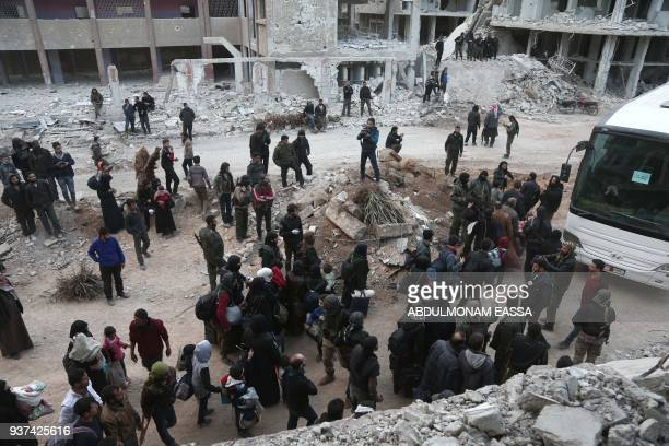 Syrians gather to board busses as they prepare to evacuate one of the few remaining rebelheld pockets in Arbin in Eastern Ghouta on the outskirts of...
