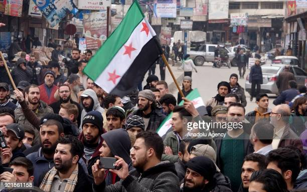 Syrians hold Syrian flags as they gather to protest against Assad Regime's blockade on Eastern Ghouta region of Damascus in Idlib Syria on February...