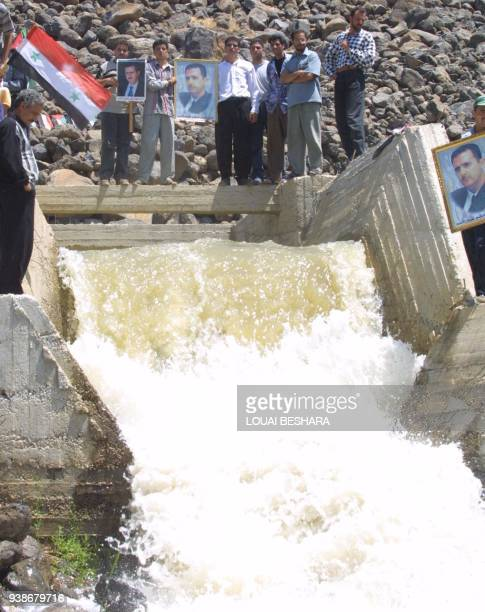 Syrians holding pictures of their president Bashar alAssad stand atop the Bassel alAssad dam in the Yarmuk valley south of Damascus 14 July 2001...