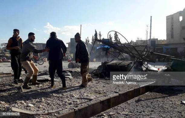 Syrians inspect a damaged building after Assad Regime carried out an airstrike to Han Seyhun of Idlib Syria on February 27 2018 The UN Security...