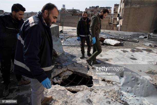 Syrians inspect a roof of a damaged building after PKK/PYD terror group fired seven missiles from Afrin region where Turkish Armed Forces conducts...