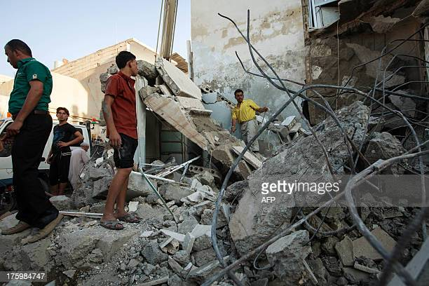 Syrians inspect debris after a bomb hit a building during clashes between rebel fighters and Syrian government forces on August 10 2013 in the...