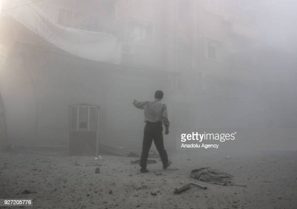 Syrians inspect destroyed buildings amid dust after Assad Regime's airstrike hit residential areas in Eastern Ghouta's Douma town despite decisions...
