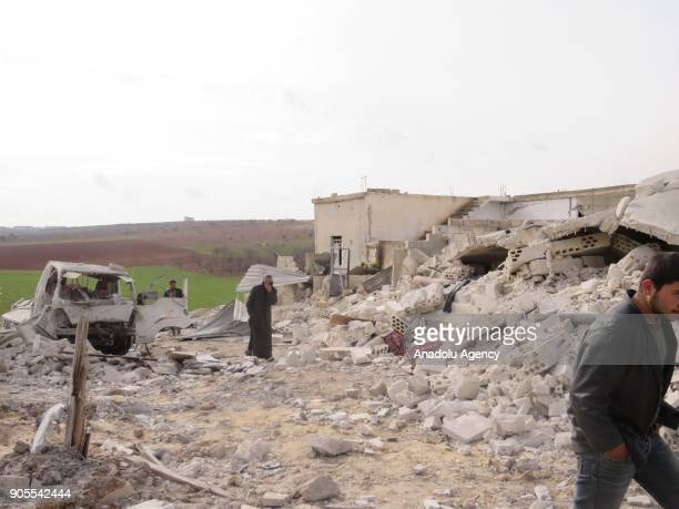 Syrians inspect the damage around the debris after an airstrike to Khan Shaykhun in Idlib Syria on January 16 2018