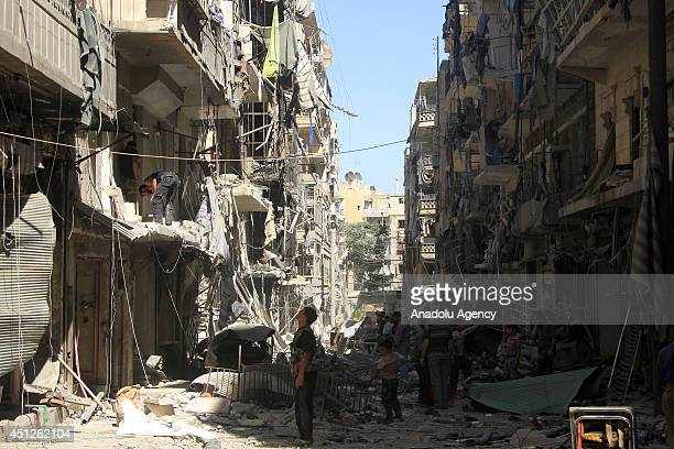 Syrians inspect the destroyed buildings following a Syrian government air strike in Aleppo, Syria, on June 26, 2014. At least 17 people including...