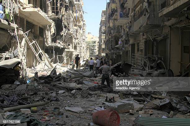 Syrians inspect the destroyed buildings following a Syrian government air strike in Aleppo Syria on June 26 2014 At least 17 people including women...