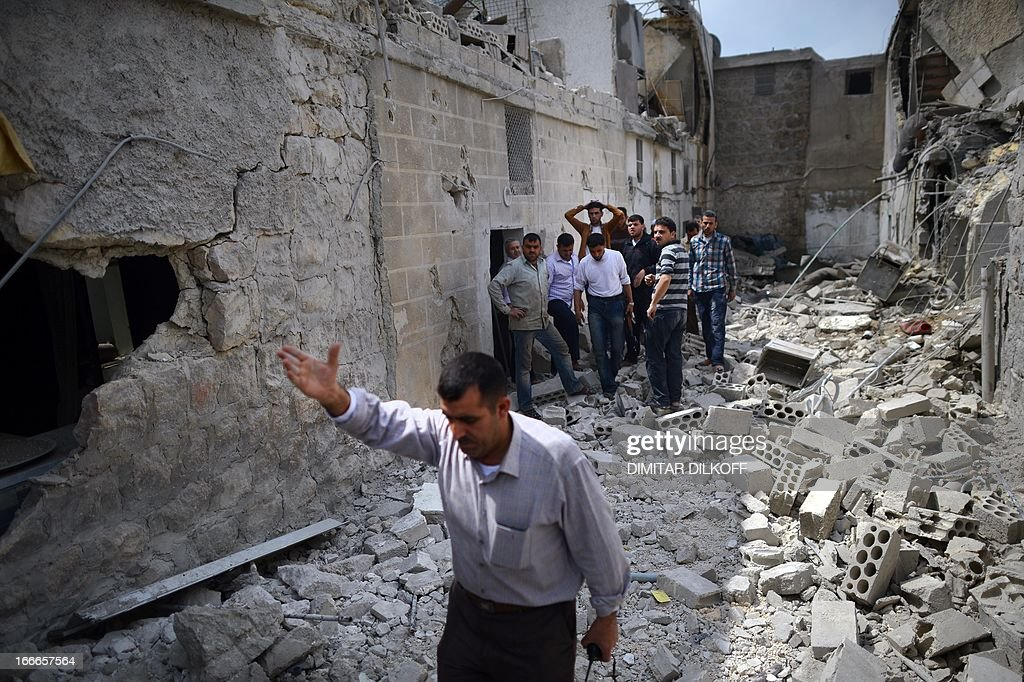 Syrians inspect the remains of destroyed houses following an airstrike by the Syrian airforce in the northern Syrian city of Aleppo on April 15, 2013. The conflict in Syria, which is now in its third year, has cost 70,000 lives, according to the United Nations.
