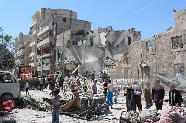 Syrians inspect the rubble of destroyed buildings following barrel bomb-attacks by Assad regime forces on a market in Maadi neighborhood of Aleppo,...