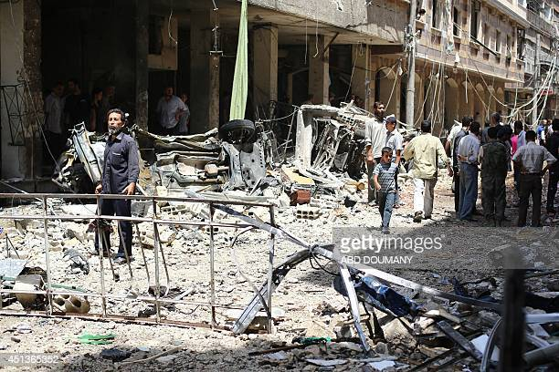 Syrians inspect the site of a reported car bomb explosion at a popular market on June 28 in the rebelheld town of Douma northeast of the capital...