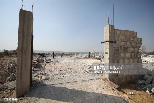 Syrians inspect the site of helicopter gunfire which reportedly killed nine people near the northwestern Syrian village of Barisha in the Idlib...