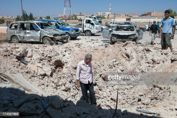 Syrians inspect the site where a barrel bomb dropped by an air force helicopter exploded in Saraqeb in northwestern Syria on July 20 2013 The Syrian...