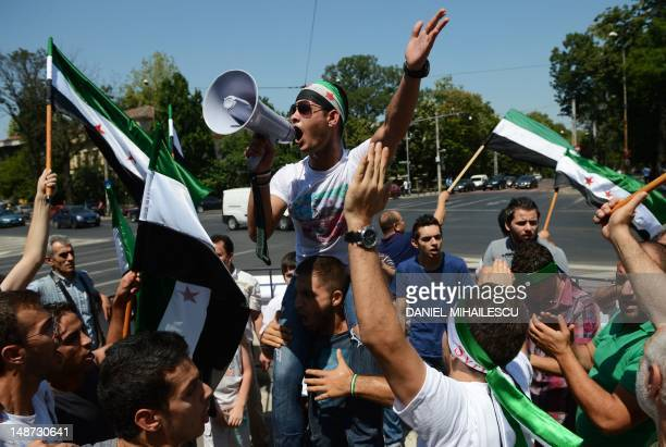Syrians living abroad in Romania hold revolutionary flags and shout slogans against Syrian President Bashar alAssad's regime in the front of Russian...