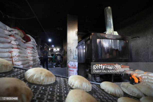 Syrians make bread in the town of Binnish in the country's northwestern Idlib province on June 9, 2020. - Syrians held a third day of rare...